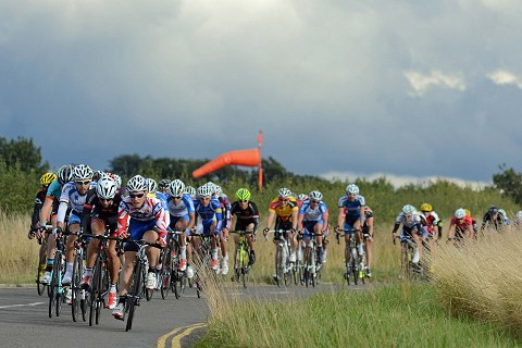The chasing bunch pass Cranfield airfield with one lap to go